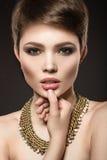 Schöne Brunettefrau mit perfekter Haut, hellem Make-up und Goldschmuck Schönes lächelndes Mädchen Lizenzfreie Stockbilder