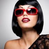 Schöne Brunettefrau mit Schussfrisur mit roter Sonnenbrille Stockbild