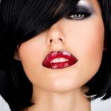 Schöne Brunettefrau mit Schussfrisur und den sexy roten Lippen Stockbild