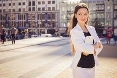 Schöne BrunetteGeschäftsfrau in der weißen Klage, die an einem Vorsprung arbeitet Stockbild