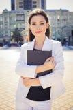 Schöne BrunetteGeschäftsfrau in der weißen Klage mit Ordner von Dokumenten in ihren Händen draußen Stockbilder