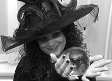 Schöne Brunettehexe, die Glaskugel Schwarzweiss hält Lizenzfreie Stockfotografie