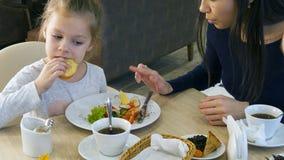 Schöne Brunettemutter, die ihre junge blonde Tochter überzeugt, Gemüsesalat im Café zu essen Lizenzfreie Stockfotos
