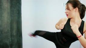 Schöne Brunetteverpackenbirne, schöner Kickboxing-Frauen-Trainingssandsack im heftigen Stärkesitz des Eignungsstudios