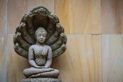 Schöne Buddha-Statue gemacht vom Sandstein und -abdeckung mit Nagaköpfen Stein-Buddha-Statue mit sieben Phaya-Naga geht voran Sto Stockfotos