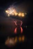 Schöne bunte Feuerwerke auf dem Wasser tauchen mit einem sauberen schwarzen Hintergrund auf Spaßfestival und internationaler Wett Stockfotografie