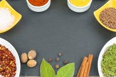 Schöne bunte Gewürze in den Schüsseln auf Schieferbehälter, Olivenöl und Salz stockfoto