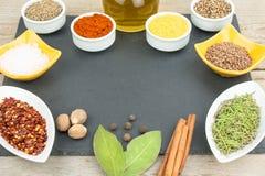 Schöne bunte Gewürze in den Schüsseln auf Schieferbehälter, Olivenöl und Salz Freier Platz für Ihren Text lizenzfreie stockfotografie