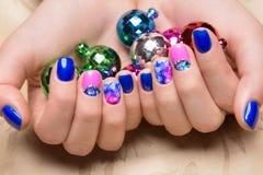 Schöne bunte Maniküre mit Blasen und Kristallen auf weiblicher Hand Nahaufnahme Lizenzfreie Stockfotos