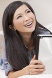 Schöne chinesische Frau, die Tablette-Computer verwendet Stockbilder
