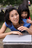 Schöne chinesische und kleine Schwester mit Laptop stockbilder