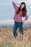 Schöne Cowboyfrau, die auf dem Gebiet aufwirft stockfotografie