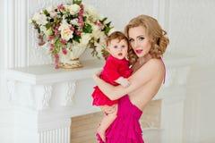 Schöne dünne blonde Mutter im roten Kleid hält ihr kleines dau Stockfotos
