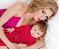 Schöne dünne blonde Mutter im roten Kleid liegt auf einem Bett nahe bei einem s Stockfotos