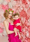Schöne dünne blonde Mutter im roten Kleid und in einem Kranz von Blumen I Lizenzfreie Stockbilder