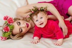 Schöne dünne blonde Mutter im roten Kleid und in einem Kranz von Blumen L Stockbilder