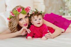 Schöne dünne blonde Mutter im roten Kleid und in einem Kranz von Blumen L Stockbild