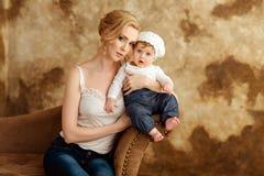 Schöne dünne blonde Mutter im weißen T-Shirt hält ein kleines Mädchen I Stockbild