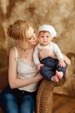 Schöne dünne blonde Mutter im weißen T-Shirt hält ein kleines Mädchen I Stockbilder