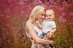 Schöne dünne blonde Mutter umarmt entzückenden kleinen Jungen, auf der Rückseite Stockfotos