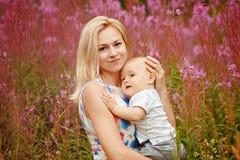 Schöne dünne blonde Mutter umarmt entzückenden kleinen Jungen, auf der Rückseite Stockfoto