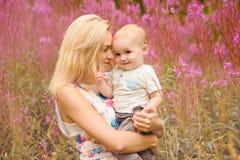 Schöne dünne blonde Mutter umarmt entzückenden kleinen Jungen, auf der Rückseite Lizenzfreies Stockfoto