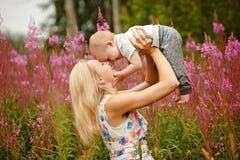 Schöne dünne blonde Mutter wirft oben und küsst das entzückende Lächeln Stockfoto