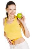 Schöne dünne Frau, die einen grünen Apfel anhält Lizenzfreie Stockfotos