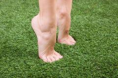 Schöne dünne weibliche Füße auf grünem Gras Stockbilder