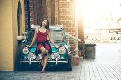 Schöne Dame Asiens, die nahe Retro- Auto steht lizenzfreie stockfotos