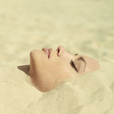 Schöne Dame begraben im Sand Lizenzfreies Stockfoto