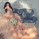 Schöne Dame in den herrlichen Couturen kleiden auf Sofa an Lizenzfreie Stockfotografie