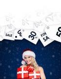 Schöne Dame in der Weihnachtskappe hält einen Satz des Geschenks Stockfotos