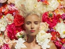 Schöne Dame, die in den Blumen liegt Stockfotografie
