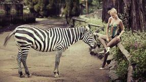 Schöne Dame, die nahe bei einem Zebra sitzt Lizenzfreie Stockbilder
