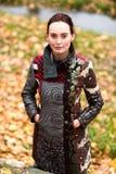 Schöne Dame im bunten Mantel wirft im Herbst auf Stockfotografie
