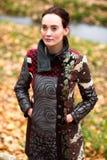 Schöne Dame im Designmantel wirft im Herbst auf Stockfoto
