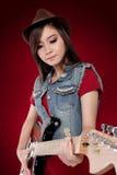 Schöne Dame im Rot, das ihre Gitarre schaukelt Stockbild