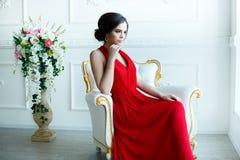 Schöne Dame im roten Kleid mit einem Abendmake-up Stockbild