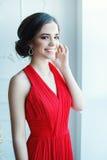 Schöne Dame im roten Kleid mit einem Abendmake-up Lizenzfreie Stockfotos