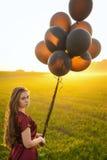 Schöne Dame im roten Kleid mit schwarzen Ballonen bei Sonnenuntergang Stockfoto