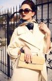 Schöne Dame mit dem dunklen Haar, das eleganten Mantel und Sonnenbrille trägt lizenzfreie stockfotos