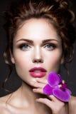 Schöne Dame mit einem Kranz von Blumen Stockfotografie