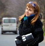 Schöne Dame mit Geldbeutel und unscharfem Auto hinter ihr Stockfotografie