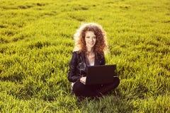 Schöne Dame mit ihrem Laptop auf Gras Lizenzfreies Stockfoto