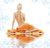 Schöne Dame mit orange Tüchern auf weißem Sand Stockfoto