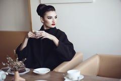 Schöne Dame mit perfektem bilden Sitzen im trinkenden Kaffee des netten Cafés und Essenkuchen stockfotos