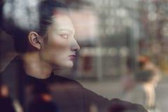 Schöne Dame mit provozierendem bilden Sitzen hinter dem Fenster und beiseite schauen lizenzfreie stockbilder