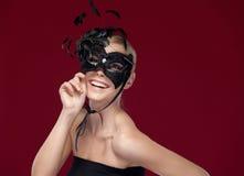Schöne Dame mit schwarzer Maskerademaske mit Federn Lizenzfreie Stockfotografie