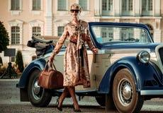 Schöne Dame mit Tasche nahe klassischem Kabriolett stockfoto
